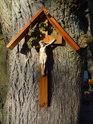 Malý křížek s Ježíšem, přibitý na na kmeni stromu u Panny Marie ve skále.